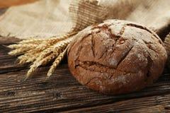 Świeżo piec chleb na brown drewnianym tle Fotografia Stock
