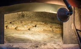 Świeżo piec chleb w nieociosanej piekarni z tradycyjnym starym kamiennym piekarnikiem Obrazy Royalty Free