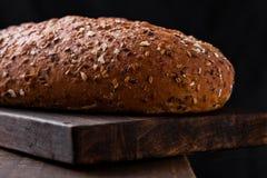 Świeżo piec chleb z owsami na drewnianej desce Zdjęcia Stock