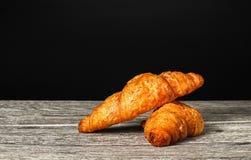 Świeżo piec croissant, świeżych i smakowitych croissants odizolowywający na drewnianym stole, czarny tło zdjęcie royalty free