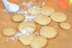 Świeżo piec cukrowi ciastka z białym lodowaceniem i tęczą barwiącymi kropią z barwionymi światłami w tle Obrazy Stock