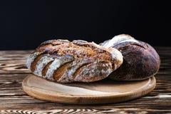 Świeżo piec robić chleb kłama na round drewnianym talerzu na czarnym tle fotografia stock