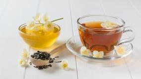 Świeżo przygotowana herbata z jaśminu miodem na stole i kwiatami Zdjęcia Royalty Free