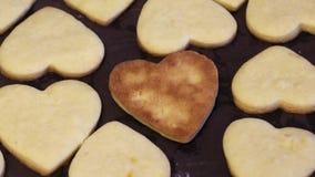 Świeżo przygotowane ciasteczka z herbatnikami leżą na kartce i chłodne Ciasteczka w kształcie serca i kwiatów Jeden jest do góry  zbiory