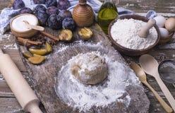 Świeżo przygotowany ciasto dla domowej roboty kulebiaka z śliwkami nad stołami z składnikami dla kulebiaka obrazy stock