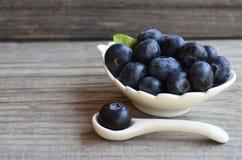 Świeżo ukradzione czarne jagody w białym pucharze na starym drewnianym tle Świeża organicznie czarna jagoda borówki obrazy stock