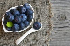 Świeżo ukradzione czarne jagody w białym pucharze na starym drewnianym tle Świeża organicznie czarna jagoda borówki obrazy royalty free