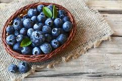 Świeżo ukradzione czarne jagody w koszu na starym drewnianym tle Świeże czarne jagody z zielonymi liśćmi na wieśniaka stole Obrazy Stock