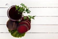 Świeży ćwikłowy sok z zieleniami w szkle na deskach Zdjęcie Royalty Free