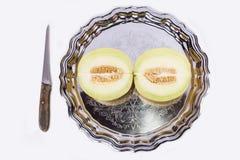 Świeży żółty kantalup ciie w połówce na starej tacy z nożem obraz royalty free