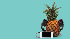 świeży ananas z czarnym smartphone z czerń ekranem przeciw błękitnemu tłu i hełmofonami zdjęcie royalty free