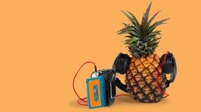 świeży ananas z czarnym wlakman pomarańcze tłem i hełmofonami obraz royalty free