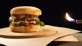 Świeży apetyczny hamburger wiruje na czarnym tle blisko istnego ogienia zbiory wideo