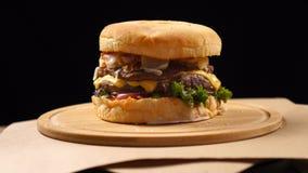Świeży apetyczny hamburger wiruje na czarnym tle zdjęcie wideo