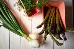 Świeży asparagus i szczypiorki na białym kuchennym stole obraz stock