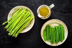 Świeży asparagus na talerzach blisko dzbanka olej na czarnego tła odgórnym widoku Obrazy Stock