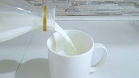 Świeży bielu mleka dolewanie w pić szkło na kuchennym tle, strzela z zwolnionym tempem, dietą i zdrowymi odżywiań breakfas, zbiory wideo
