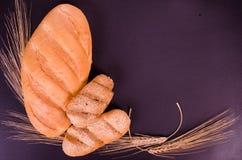 Świeży chleb, babeczki i pszeniczni ucho w czarnym tle, Zdjęcie Royalty Free