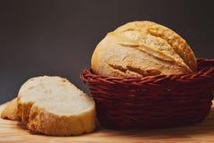 Świeży chleb robić od pszenicznej mąki w łozinowym koszu robić ciemny drewno kłama na drewnianej desce i przeciw ciemnemu tłu świ zdjęcie royalty free