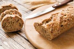 Świeży chleb z słonecznikowymi ziarnami, sezamowi ziarna i len, ciiemy w kawałki na tnącej desce zdjęcia royalty free