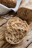 Świeży chleb z słonecznikowymi ziarnami, sezamowi ziarna i len, ciiemy w kawałki na tnącej desce zdjęcia stock