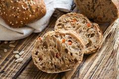 Świeży chleb z słonecznikowymi ziarnami, sezamowi ziarna i len, ciiemy w kawałki na tnącej desce zdjęcie royalty free