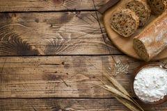 Świeży chleb z słonecznikowymi ziarnami, sezamowi ziarna i len, ciiemy w kawałki na tnącej desce Drewniany tło, kopii przestrzeń obraz stock