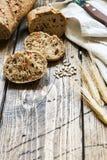 Świeży chleb z słonecznikowymi ziarnami, sezamowi ziarna i len, ciiemy w kawałki na tnącej desce Drewniany tło, kopii przestrzeń obrazy stock