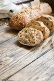 Świeży chleb z słonecznikowymi ziarnami, sezamowi ziarna i len, ciiemy w kawałki na tnącej desce Drewniany tło, kopii przestrzeń fotografia stock