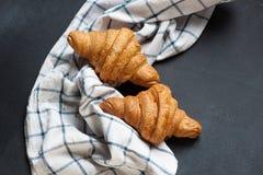 Świeży croissant lying on the beach na czarnym stole Zdjęcia Stock