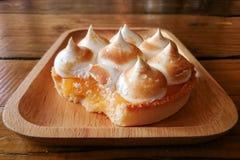 Świeży cytryny tarta w drewnianym talerzu na stole z łyżkować troszkę fotografia stock