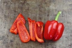 Świeży czerwony dzwonkowego pieprzu capsicum i niektóre rżnięci kawałki Zdjęcia Royalty Free