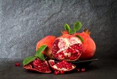 Świeży czerwony granatowiec i ziarno z liśćmi nad czerń kamieniem Zdjęcia Stock