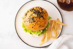Świeży domowej roboty hamburger z czarnymi sezamowymi ziarnami w talerzu z francuskich dłoniaków grulami Odgórny widok kosmos kop fotografia royalty free