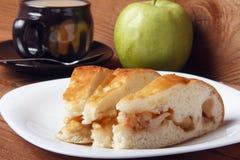 Świeży domowej roboty jabłczany kulebiak i herbata z mlekiem na drewnianym tle zdjęcia royalty free