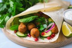 Świeży Falafel opakunek z ziele i warzywami, Jarski posiłek obrazy royalty free