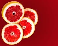 Świeży grapefruitowy i plasterki odizolowywający na gradientowej czerwieni Zdjęcia Royalty Free