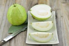 Świeży guava cięcie na talerzu na drewnianym stole Fotografia Stock