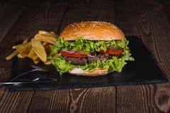 Świeży hamburgeru i francuza dłoniaków zbliżenie na drewnianym stole Fotografia Stock