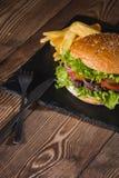 Świeży hamburgeru i francuza dłoniaków zbliżenie na drewnianym stole Zdjęcia Stock