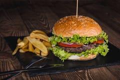 Świeży hamburgeru i francuza dłoniaków zbliżenie na drewnianym stole Obrazy Stock