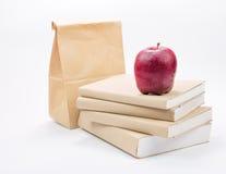 Świeży jabłko na stercie stare książki, odosobnionej na bielu Obrazy Stock
