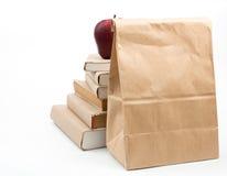 Świeży jabłko na stercie stare książki, odosobnionej na bielu Zdjęcie Stock