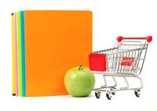 Świeży jabłko z ćwiczenia wózek na zakupy i książkami Fotografia Stock