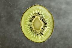 Świeży kiwi owoc plasterek na zamazanym tle Zdjęcia Stock