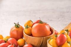 Świeży kolor żółty i czerwoni czereśniowi pomidory w koszu na cementujemy deskę, zamykamy w górę, kopii przestrzeń, odgórny widok zdjęcia royalty free