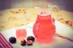 Świeży kompot śliwki w dekantatorze na stole Zdjęcie Royalty Free
