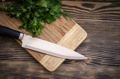 Świeży koper i pietruszka na tnącej desce z nożem na drewnianym stole Zdjęcie Royalty Free