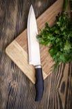 Świeży koper i pietruszka na tnącej desce z nożem na drewnianym stole Fotografia Royalty Free