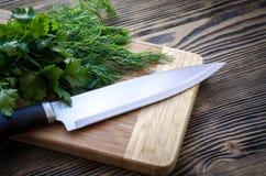 Świeży koper i pietruszka na tnącej desce z nożem na drewnianym stole Fotografia Stock